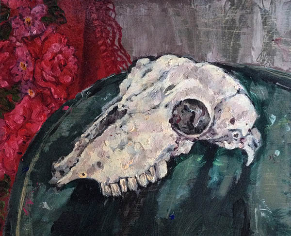 A rectangular oil painting of a sheep's skull by Nina Packer; viewed from the side it is painted in whites and pale pink loose brushstrokes and it set on a green circular table, with a red Russian scarf set to the left in the background.