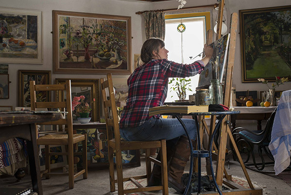 A photograph of Nina Packer painting at an easel in the New Gallery studio, she is seated and viewed side on, there are beautiful paintings on the walls behind her and still life set up on a table with oranges and a skull, which she is painting.