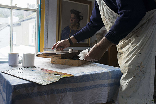 an artists palette and wooden paint box are on a table in front of a window, we can see a mans hands putting paint down, and a section of his apron covered in paint. The colours of the oil paints on the palette are bright in the sunshine