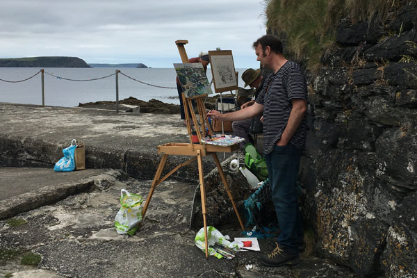 A landscape format photograph of a group of artists plein air painting on wooden easels against a rock wall, in the middle ground there you can see blue silver sea, in the background Nare headland and The Dodman, artists are Andrew Tozer, Eric Ward and Chris Insoll distance