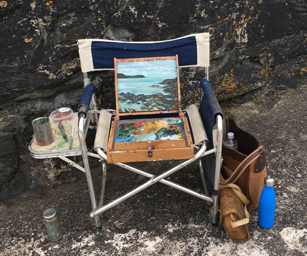 A square format photograph of an open pochade paintbox on a foldable chair, there is an old tan canvas bag next to it with a water bottle and artists materials, and an old tin can being used for turps. The painting in the box is of the sea and rocks being exposed by the tide. The chair is against rocks in part sunshine, the rocks have bright yellow lichen patches.